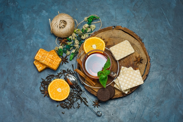 Thé Dans Une Tasse Avec Des Herbes, Orange, épices, Biscuits, Fil, Vue De Dessus De La Passoire Sur Planche De Bois Et Fond De Stuc Photo gratuit