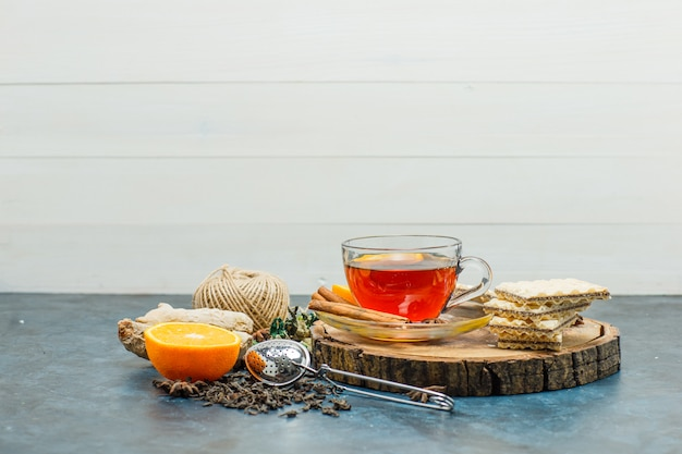 Thé Dans Une Tasse Avec Des Herbes, Orange, épices, Gaufre, Fil, Planche De Bois, Vue Latérale De La Passoire Sur Fond Blanc Et Stuc Photo gratuit