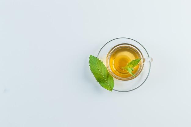 Thé Dans Une Tasse Avec Des Herbes à Plat Sur Un Fond Blanc Photo gratuit