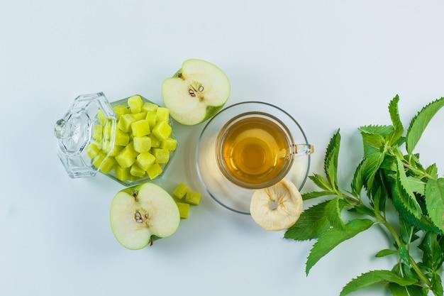 Thé Dans Une Tasse Avec Pomme, Fruits Secs, Cubes De Sucre, Herbes à Plat Sur Un Fond Blanc Photo gratuit