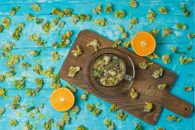 Thé Dans Une Tasse En Verre Avec Orange, Herbes Séchées Vue De Dessus Sur Planche à Découper Et Bleu Photo gratuit