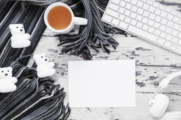 Thé et écharpe près de la feuille de papier et des appareils Photo gratuit
