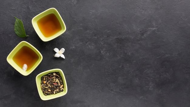Thé frais aux herbes séchées et fleur de jasmin sur une surface noire Photo gratuit