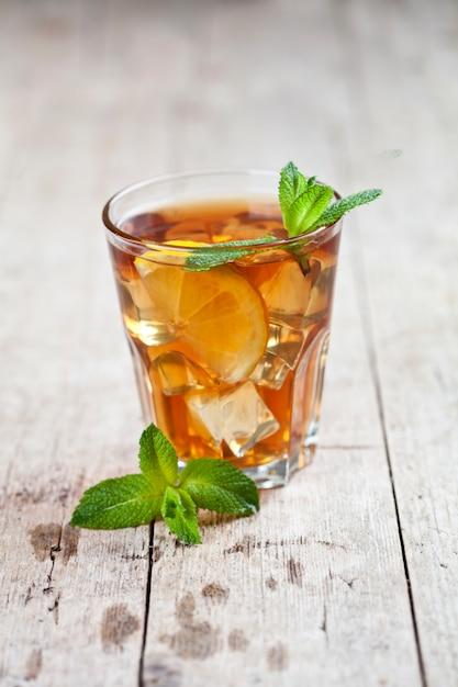 Thé glacé traditionnel au citron, feuilles de menthe et glace en verre sur une table en bois rustique Photo Premium