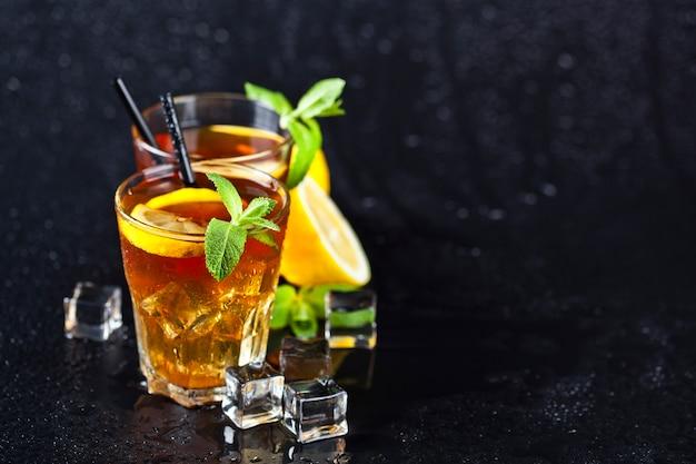 Thé glacé traditionnel au citron, feuilles de menthe et glaçons dans deux verres sur fond noir humide. Photo Premium
