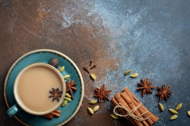 Thé indien masala chai. thé épicé au lait sur fond rouillé foncé Photo Premium