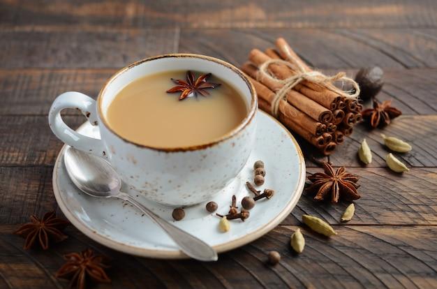 Thé indien masala chai. thé épicé au lait sur la table en bois rustique. Photo Premium