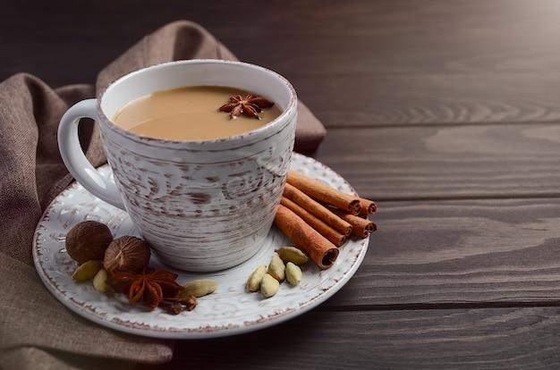 Thé indien masala chai. thé épicé au lait sur la table en bois sombre. Photo Premium