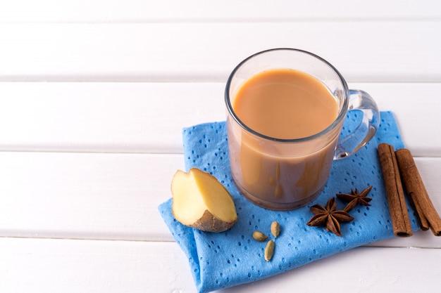Thé masala chai dans un verre et des herbes de la cuisine sur une table blanche Photo Premium