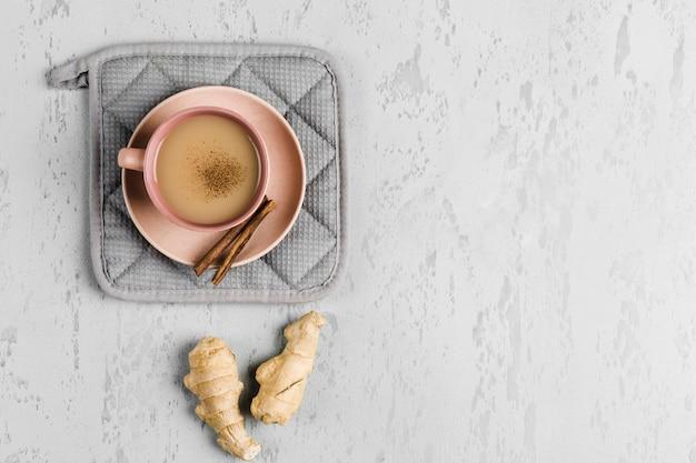 Thé masala dans une tasse sur l'assiette avec des épices d'hiver à la cannelle et au gingembre Photo Premium