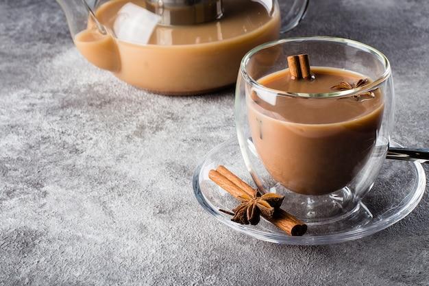 Thé masala dans une tasse en céramique avec des épices Photo Premium