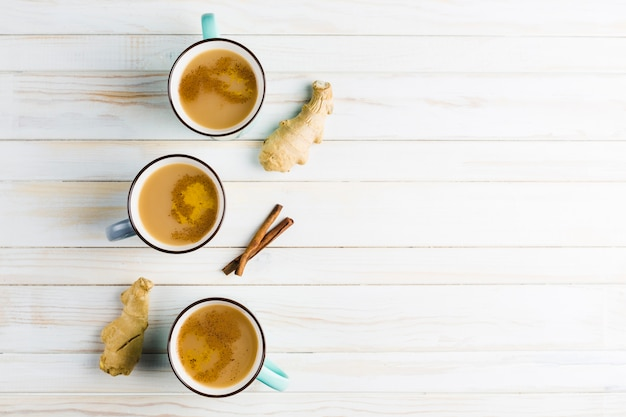 Thé masala dans des tasses en céramique avec des épices d'hiver à la cannelle et au gingembre Photo Premium