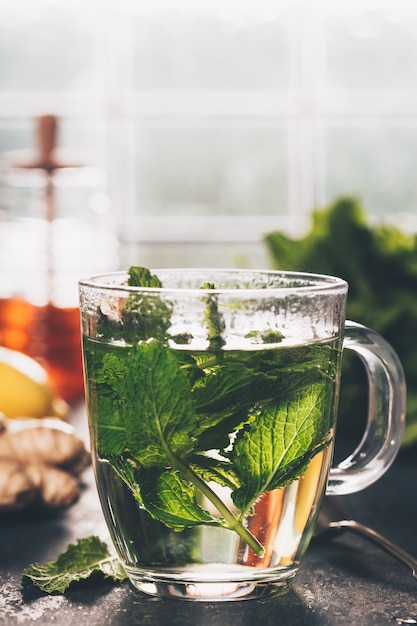 Thé à la menthe fraîche près de la fenêtre. maison confortable ou santé Photo Premium