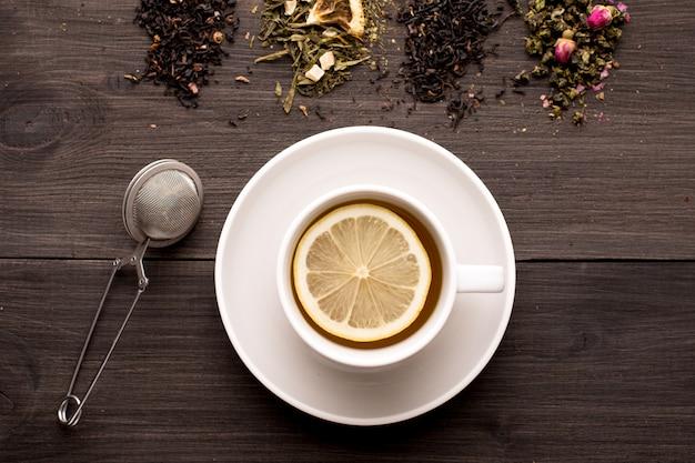 Thé noir au citron et plusieurs vues de thé sur une table en bois Photo Premium