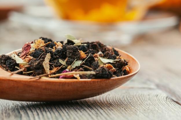Thé noir aux herbes dans des cuillères en bois sur une planche de bois Photo Premium