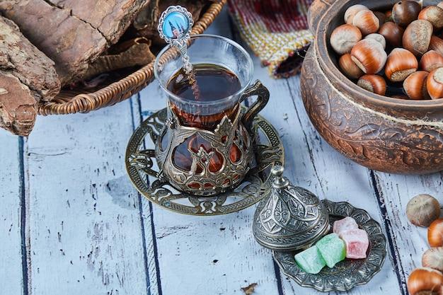 Thé Noir Dans Une Tasse En Verre Traditionnelle Avec Des Bonbons Et Un Bol De Noisettes Sur Table En Bois Bleu Photo gratuit