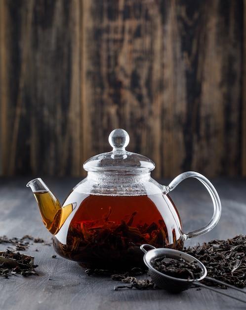 Thé Noir Avec Du Thé Sec Dans Une Théière Sur Une Surface En Bois Photo gratuit
