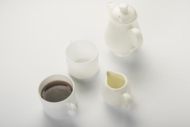 Thé noir; pot à lait; tasse blanche et théière isolé sur fond blanc Photo gratuit