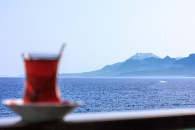Thé noir turc en verre traditionnel sur fond de mer bleue de la méditerranée Photo Premium