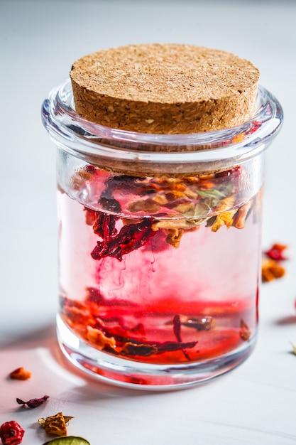 Thé Rose Baies Aux Herbes Dans Un Bocal En Verre, Fond Blanc. Contenu De Boissons Saines. Photo Premium