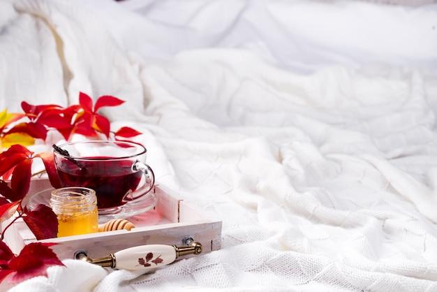 Thé rose chaud et sain sur un plateau en bois avec des feuilles mortes de l'automne sur une couverture en laine chaude et tricotée Photo Premium