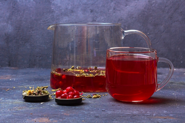 Thé Rouge (rooibos, Hibiscus, Karkade) En Tasse En Verre Et Théière Parmi Les Feuilles De Thé Séchées, Photo Premium