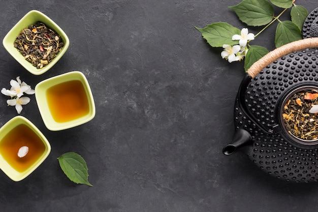 Thé sain biologique cru et son ingrédient sur une surface noire Photo gratuit