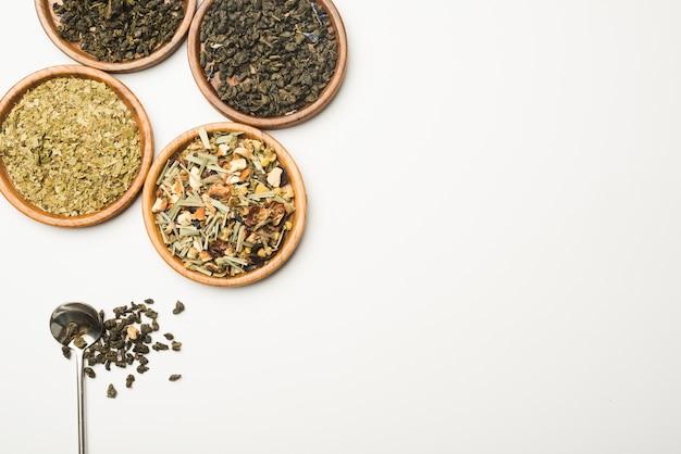 Thé séché aux herbes sur des plats ronds en bois sur fond blanc Photo gratuit