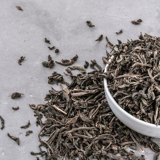 Le Thé Séché Est Versé Dans Une Tasse En Céramique Blanche Sur Un Fond Texturé Gris. Photo Premium