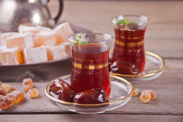 Thé turc dans des tasses en verre traditionnelles sur la table en bois Photo Premium