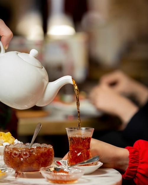 Thé versé dans le verre armudu de la théière servi avec de la confiture Photo gratuit