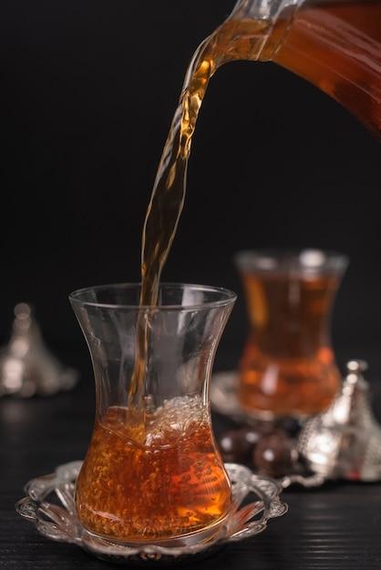 Thé versé dans un verre transparent Photo gratuit