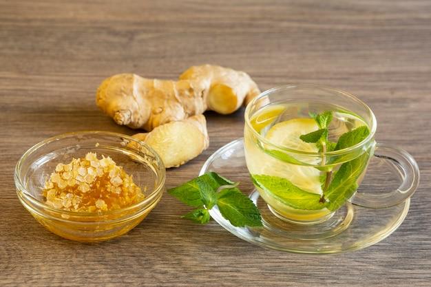Thé Vert Au Citron Et Menthe, Gingembre Et Miel Dans Un Bol En Verre Sur Une Table En Bois Photo Premium
