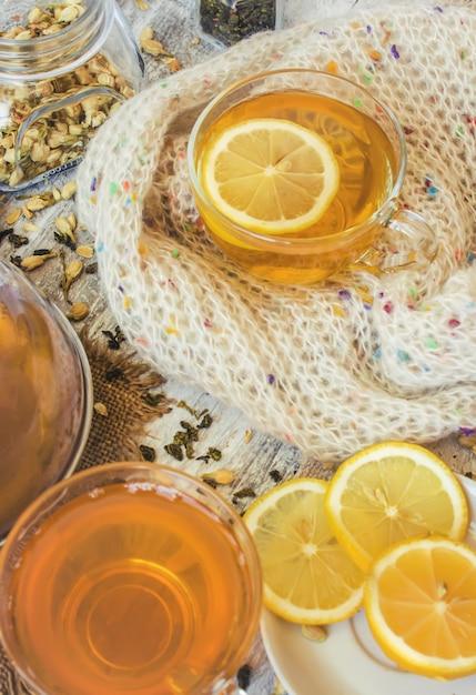 Thé vert au jasmin et noir avec citron transparent dans une petite tasse sur un fond clair. la théière mise au point sélective. Photo Premium