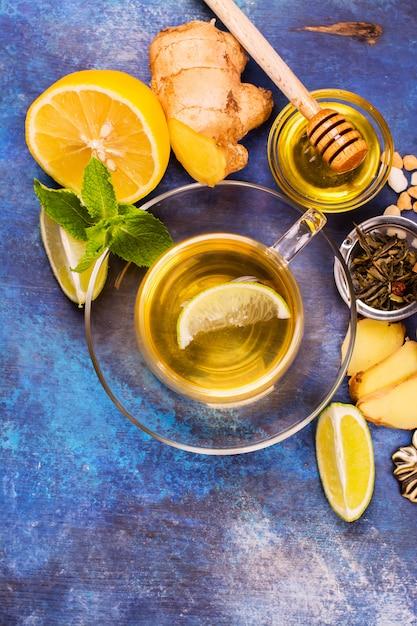 Thé vert chaud dans une coupe en verre servie avec citron, gingembre, citron vert, miel et menthe sur fond en bois bleu grunge. vue de dessus. Photo Premium