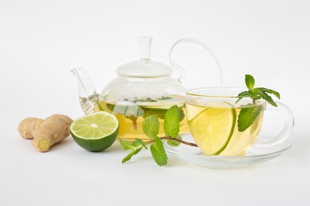 Thé Vert Dans Une Tasse En Verre Et Théière, Feuilles De Menthe, Citron Vert Et Gingembre Sur Un Tableau Blanc Photo Premium