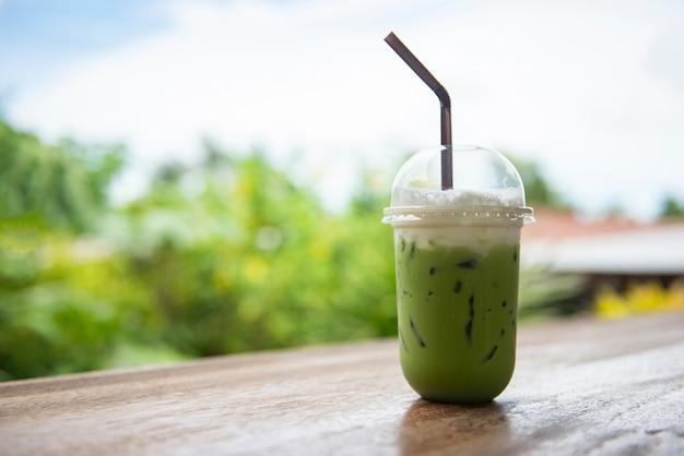 Thé Vert Glacé Dans Une Tasse En Plastique / Thé Vert Matcha Frappé Au Latte Et Paille Sur Une Table En Bois Avec La Nature Photo Premium