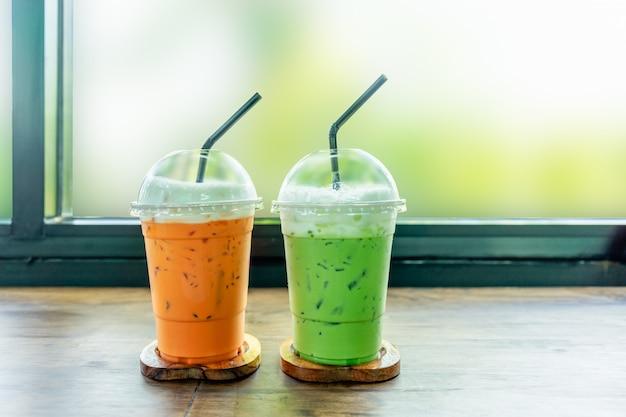 Thé vert glacé et thé glacé thaïlandais sur une table en bois. Photo Premium