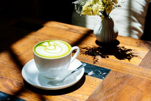 Thé vert matcha au lait dans une tasse blanche Photo gratuit