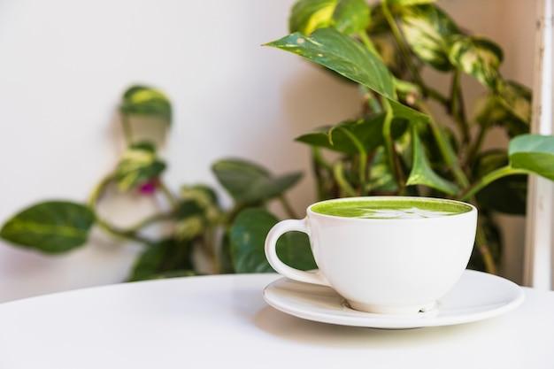 Thé vert matcha chaud dans une tasse sur une soucoupe sur la table blanche Photo gratuit