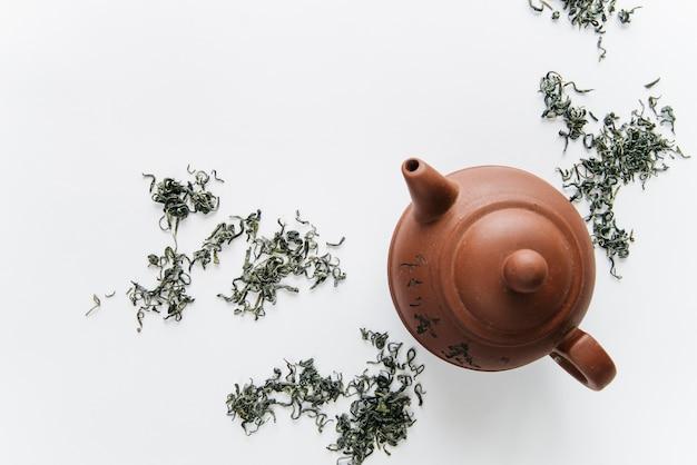 Théière en argile chinoise aux herbes séchées isolé sur fond blanc Photo gratuit