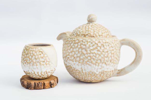 Théière beige et tasse en céramique avec fond blanc Photo Premium