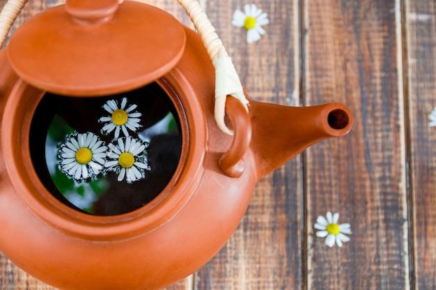 Théière brune ouverte avec thé et fleur de camomille sur une surface en bois Photo Premium