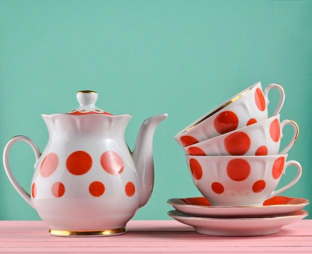 Théière En Céramique, Une Pile De Tasses à Pois Sur Une Table En Bois Isolée. Espace Copie Photo Premium