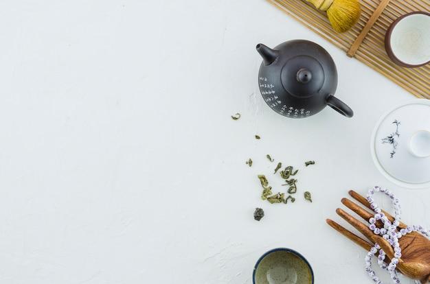 Théière en céramique et tasses aux herbes isolés sur fond blanc Photo gratuit