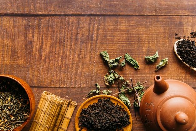 Théière chinoise traditionnelle avec des feuilles de thé et napperon sur un bureau en bois Photo gratuit