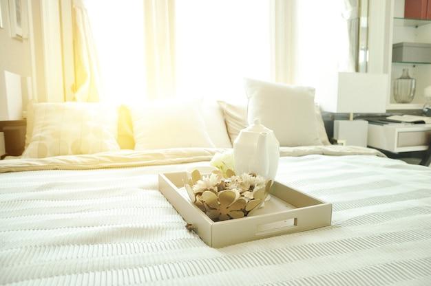 Théière dans le panier sur le lit blanc. Photo Premium