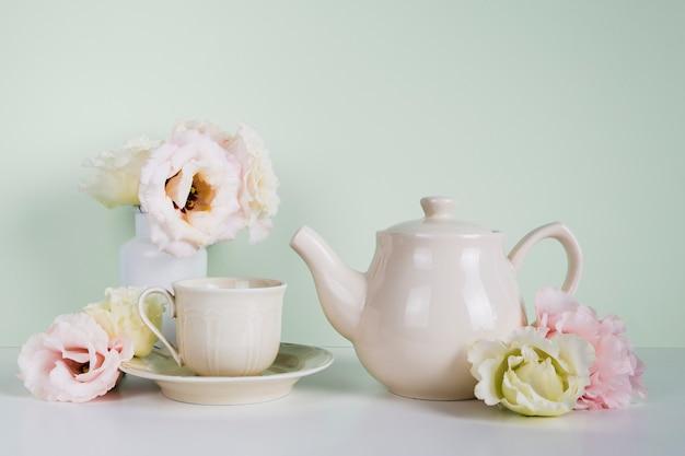 Théière élégante à côté de fleurs Photo gratuit