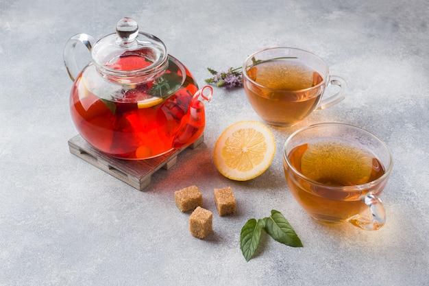 Théière en verre avec thé, menthe et citron sur une table grise avec espace de copie Photo Premium