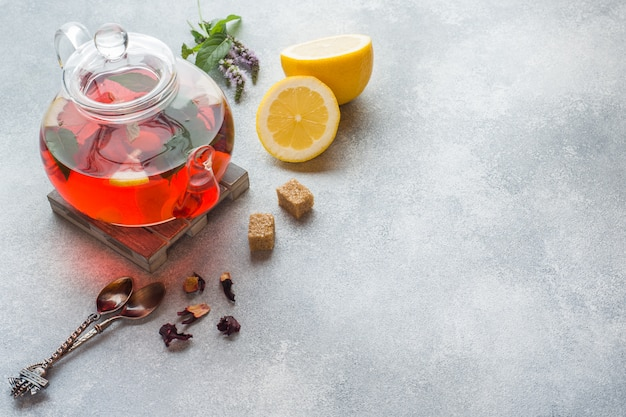 Théière en verre avec thé, menthe et citron sur une table grise avec espace de copie. Photo Premium